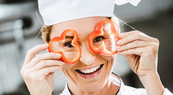 smiling female chef in double-breasted jacket holding pepper slices in front of face in restaurant kitchen